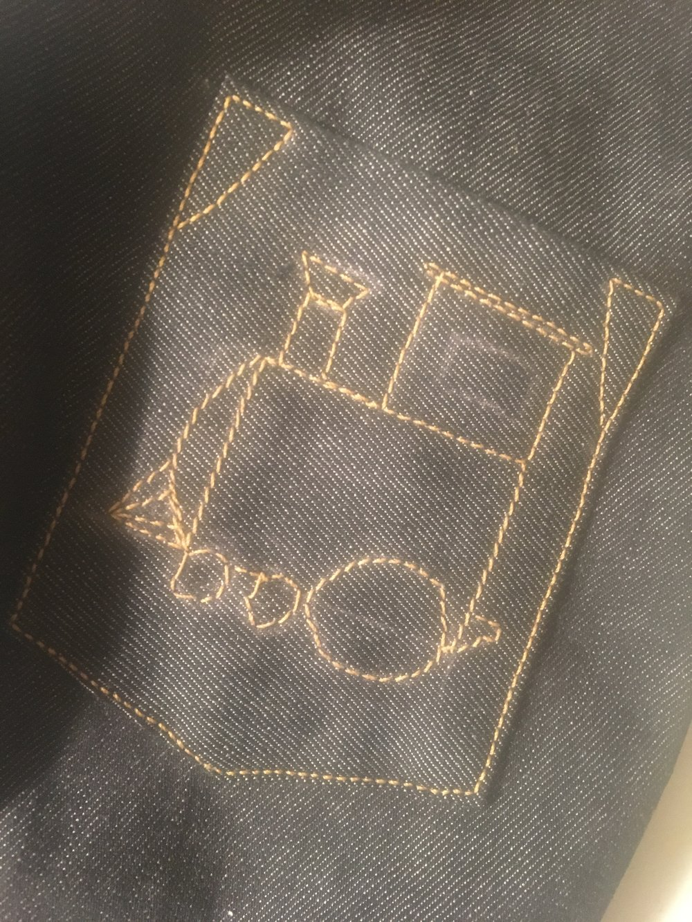 back pocket topstitching which includes a simple train picture and triangle top reinforcements along with edgestitching