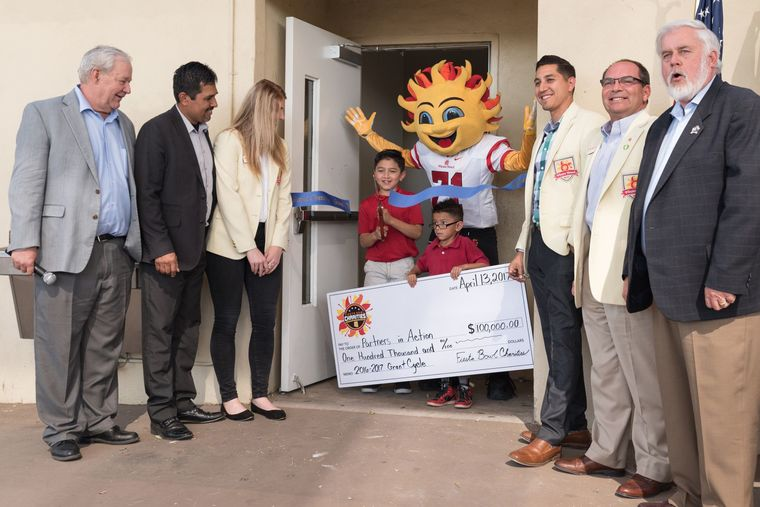 Photo courtesy City of Glendale Pictured at the Glendale Community Center ribbon-cutting: Partners in Action CEO Jerry Bowman, Glendale City Councilmember Jamie Aldama, Fiesta Bowl Charities Community Relations Coordinator Kelly Schindler, Fernando and Isreal Trejos, Fiesta Bowl mascot Spirit, Fiesta Bowl Director of Marketing and Community Relations Jose Moreno, Fiesta Bowl board of directors member Gary Hanson and Mayor Jerry Weiers.