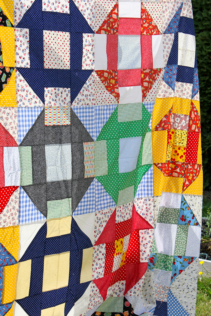 Primary Colors Supersize Churn Dash Quilt Finished via www.helloquilting.com
