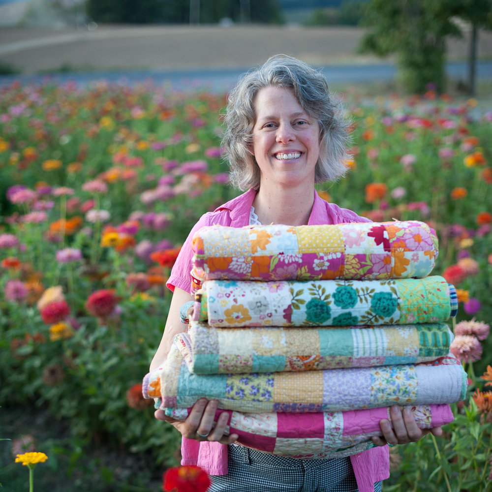 Angela Guzzo from Hello, Quilting! with a Stack of Quilts