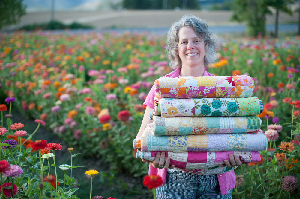 Angela Holding a Stack of Quilts via www.helloquilting.com