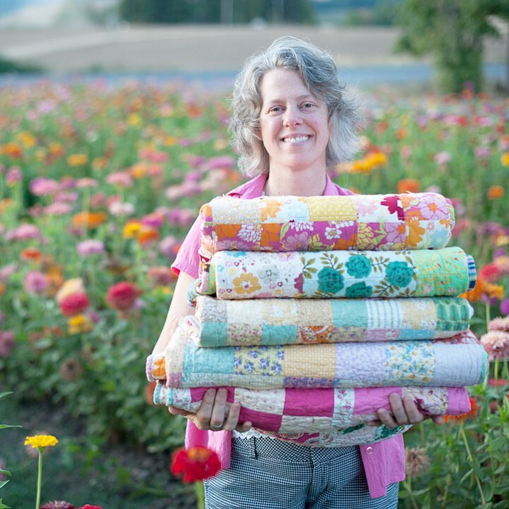 Angela from Hello, Quilting! with a stack of quilts.