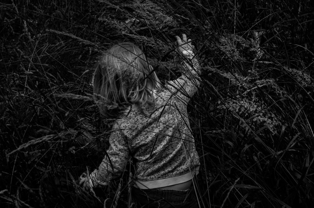 A little girl moves through the grass that is too high for her. Photograph by Kristine Nyborg