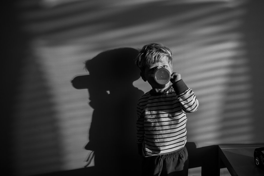A child drinks his morning milk in dappled light in Vancouver, British Columbia. Image by Kristine Nyborg / Wild Blueberry Photography