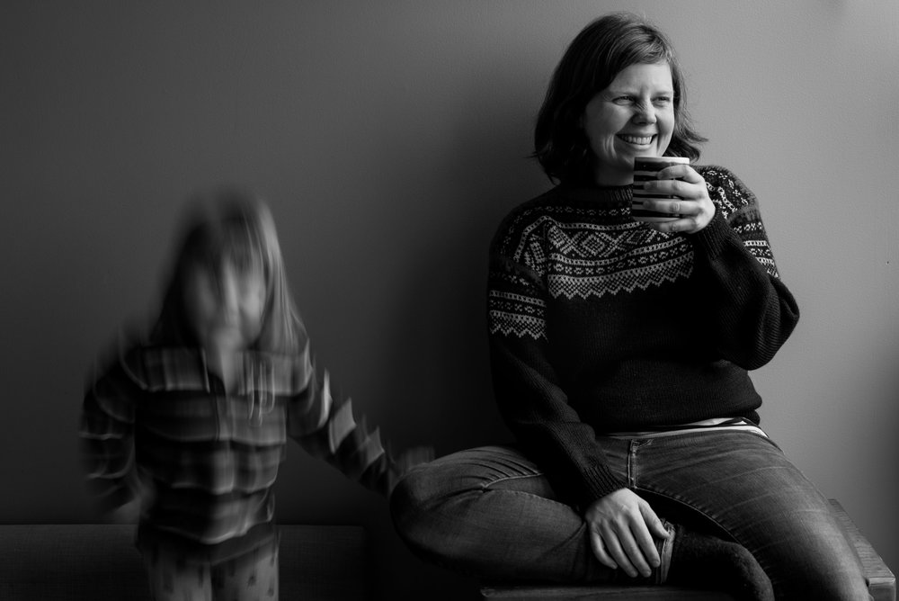 A child bounces on the couch while her mom tries to enjoy a cup of coffee, near Vancouver, British Columbia. Photography by Kristine Nyborg / Wild Blueberry Photography