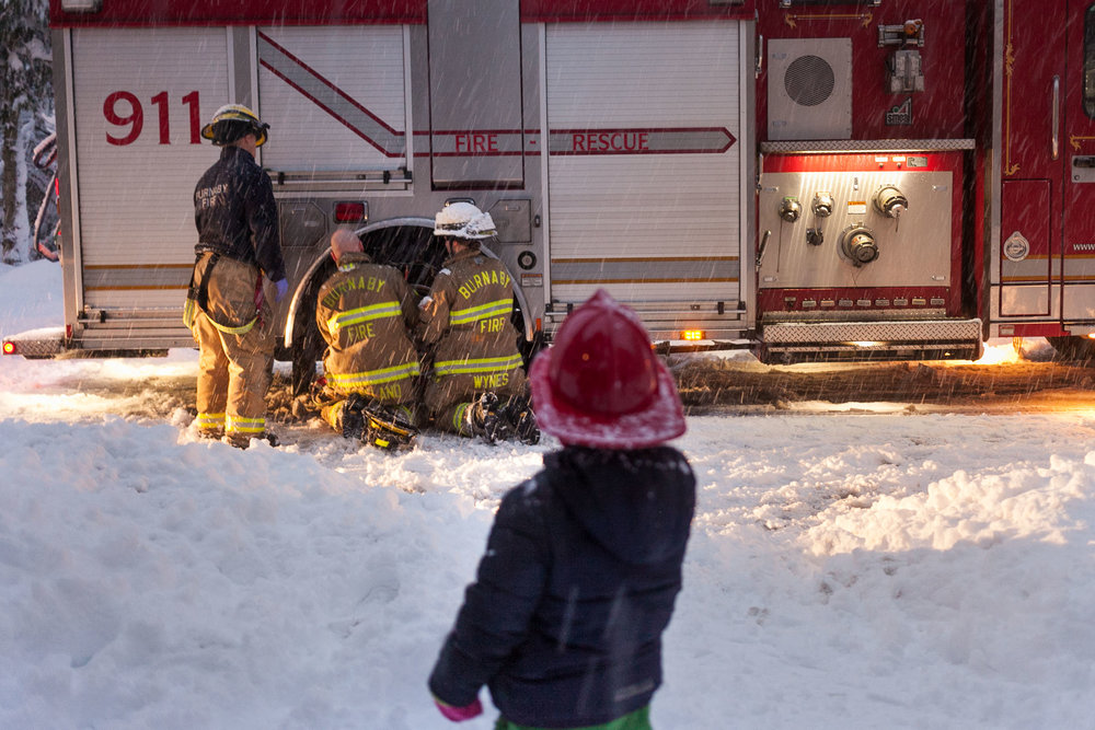 Child watches Burnaby Fire Dept firefighters put chains on their tires during a Vancouver snow storm. Before they started their work they made sure to give the children watching a plastic fire helmet each.