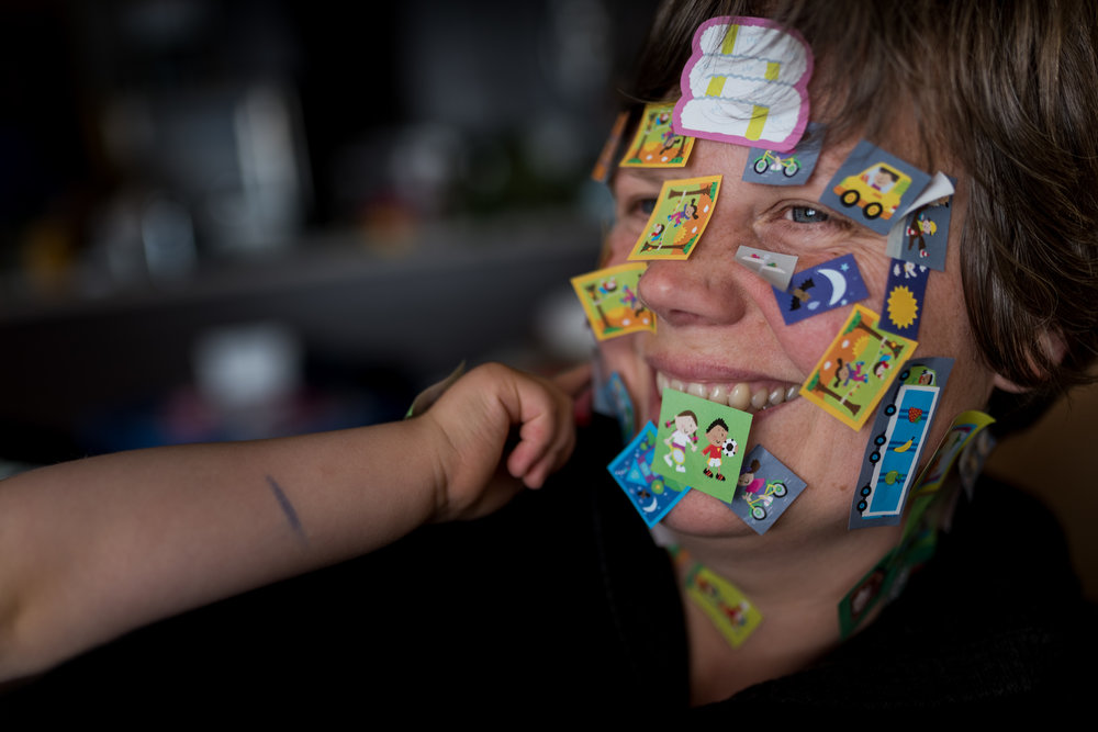 A mother being covered in stickers by her daughter.  Vancouver, British Columbia.