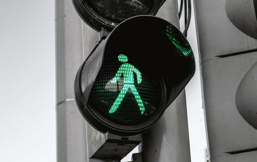 Cross Now! A green man at the pedestrian traffic lights.