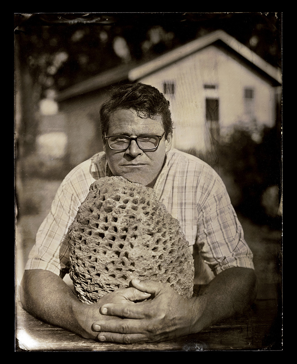 Kirk Johnson    Wet Plate Tintype on Aluminum   Dr. Kirk Johnson is Sant Director of the Smithsonian's National Museum of Natural History and an esteemed paleobotanist. For the last 36 years, Dr. Johnson has been researching the fossil plants of the Hell Creek Formation in Montana and North Dakota. Dr. Johnson is pictured with a petrified cycadeoid trunk from the Early Cretaceous that was discovered in the Black Hills of South Dakota.
