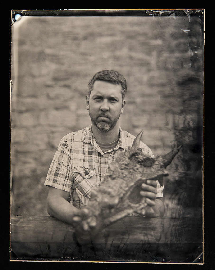 """Dave Evans    Wet Plate Tintype on Aluminum   Dr. Dave Evans is the Temerty Chair &Senior Curator in Vertebrate Paleontology at the Royal Ontario Museum in Toronto, Canada. His current research program at the ROM focuses on the evolution and paleobiology of dinosaurs and their role in the Late Cretaceous terrestrial ecosystems. Dr. Evans and his lab use fossils collected in Montana to research patterns of dinosaur diversity, ecology, evolution and evaluate how they relate to environmental changes leading up to the end-Cretaceous extinction event. Dr. Evans is pictured here holding a skull of """"Dracorex hogwartsia"""", the enigmatic bone-headed dinosaur named in honor of author J.K. Rowling, but now thought to be a juvenile form of the famous Pachycephalosaurus. Specimen courtesy of the Carter County Museum collections in Ekalaka Montana"""