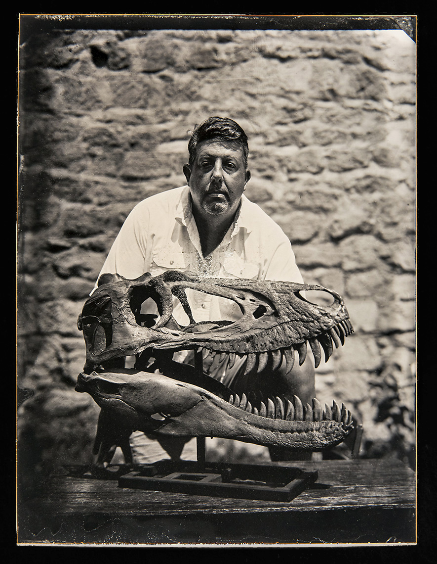 """Scott A. Williams    Wet Plate Tintype on Aluminum   Scott Williams is the paleontology lab and field specialist with the Museum of the Rockies at Montana State Univeristy. He's been conducting fieldwork in Montana for nearly two decades with MOR and the Burpee Museum of Natural History. Scott served as the chief fossil preparator in charge of """"Jane"""" the most famous Juvenile Tyrannosaurus rex specimen ever discovered. Scott is pictured here with the cast skull of Jane from the collections of the Carter County Museum in Ekalaka, Montatna."""