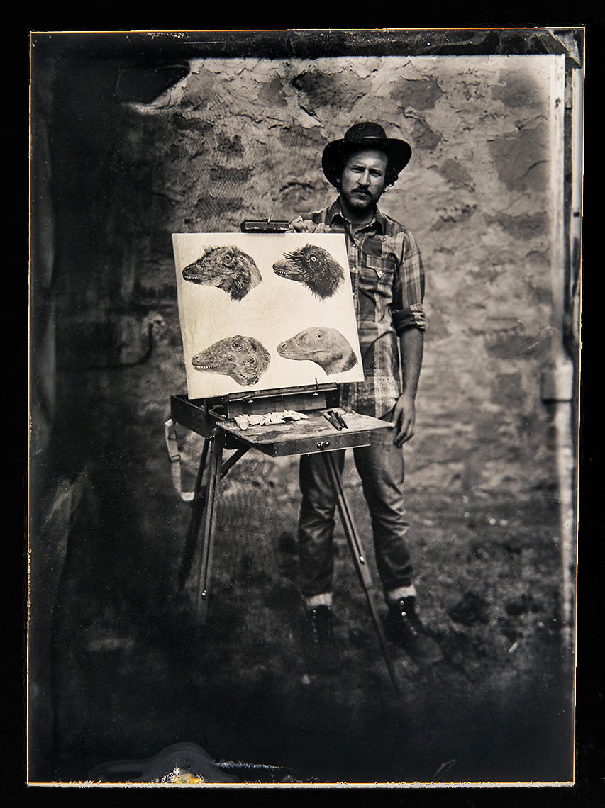 Xan Peters    Wet Plate Tintype on Aluminum   Xan Peters is currently the paleoartist in residence at the Carter County Museum in Ekalaka, Montana. His work takes imaginative leaps to recreate the world of extinct life using the limited conctete evidence provided by paleontologists. Xan is pictured here with a watercolor study he is using to understand soft-tissue on latest Cretaceous aged raptors.