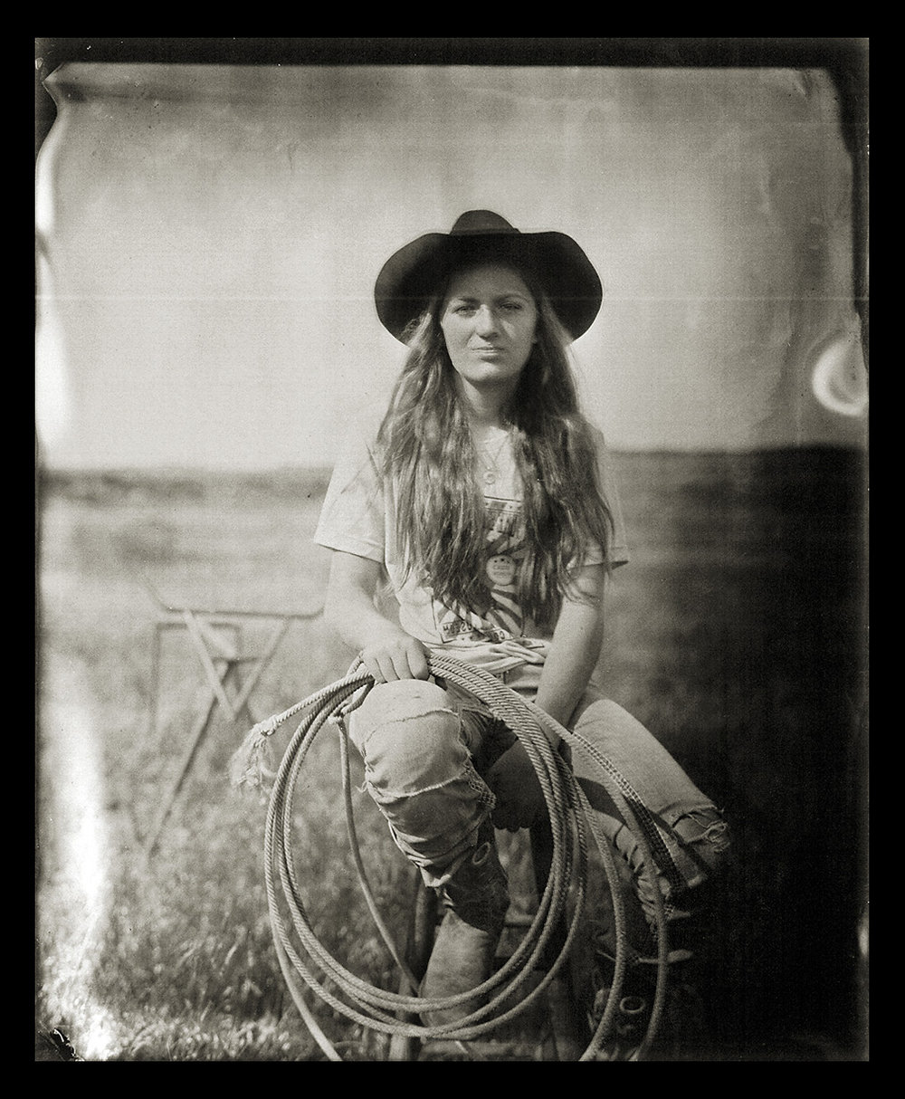 Jaden Stauffer    Wet Plate Tin Type on Aluminum   Jaden Stauffer is the youngest family member still living and working on the Zerbst Ranch in Niobrara County Wyoming, just outside of the Black Hills. Jaden is a 5th generation rancher, fossil collector and an avid photographer. The ranch she calls home has produced some of the world's most incredible fossils of Tyrannosaurus rex, Edmontosaurus, and Triceratops.Since their discovery in the early 1900's, the much celebrated 'mummified' dinosaurs from this ranch have been important elements on exhibit in New York and Seckenberg, Germany. She is photographed here on her ranch with her lariat and roping steer.