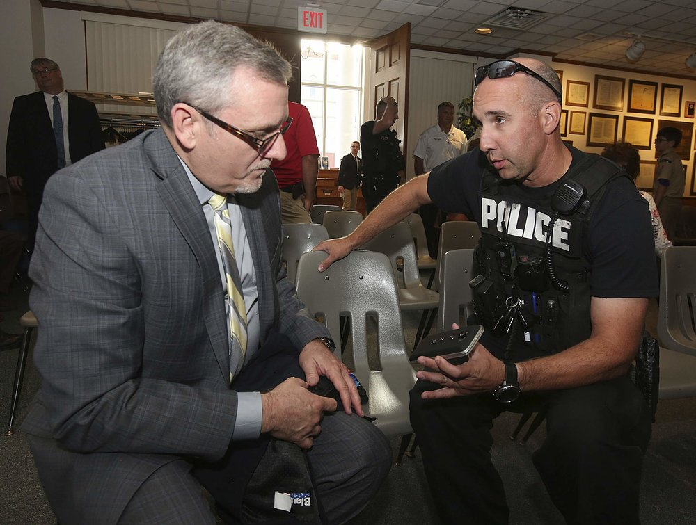Quincy Police K-9 officer Mike Tyler, right, chats with Mark Wood, a business manager for Bodyworn Utilities Inc., after Wood gave a presentation on police body cameras to the Quincy City Council Monday, June 4, 2018, at City Hall. Tyler is holding one of the cameras, which are based on a Motorola Moto-E cell phone platform. | H-W Photo/Phil Carlson