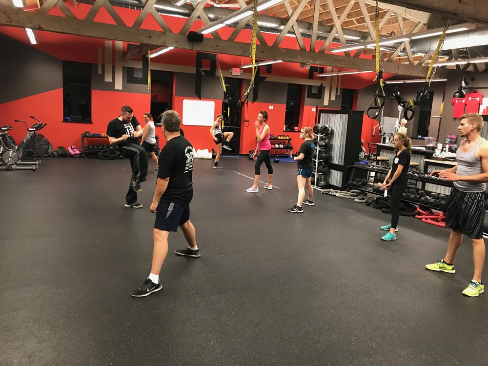Students first observe Krav Maga self-defense techniques at full speed then watch each part broken down before practicing it with partners.