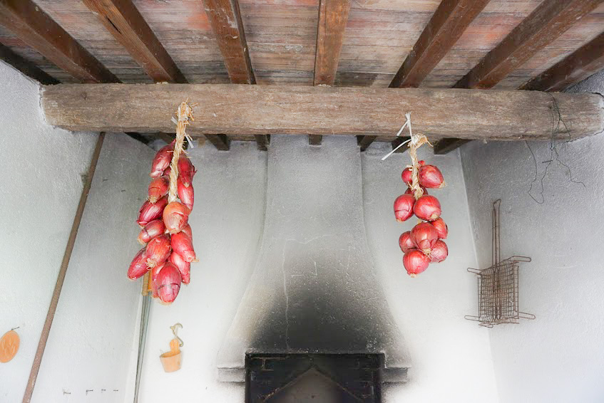 Hanging onions on the Ortaglia property. Braiding onions provides better air circulation than storing them in a bin.