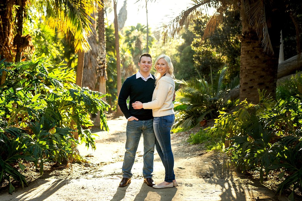 Cora and Zach pose for an engagement picture in the Palm court of Balboa Park in San Diego.