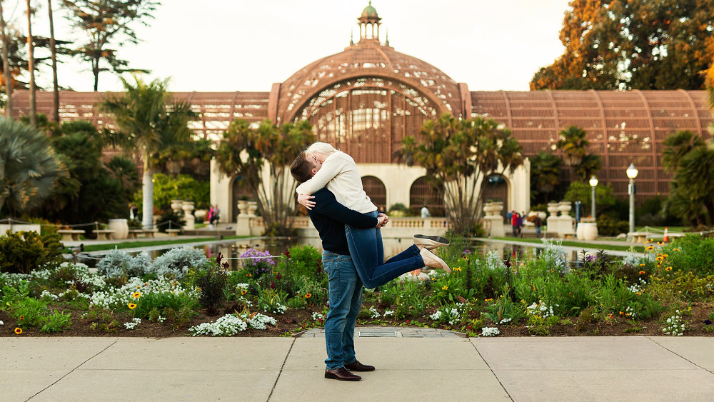 Zach lifts Cora in front of the Botanical building in Balboa Park, San Diego