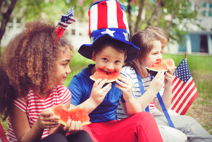 kids wearing red, white, and blue eating watermelon