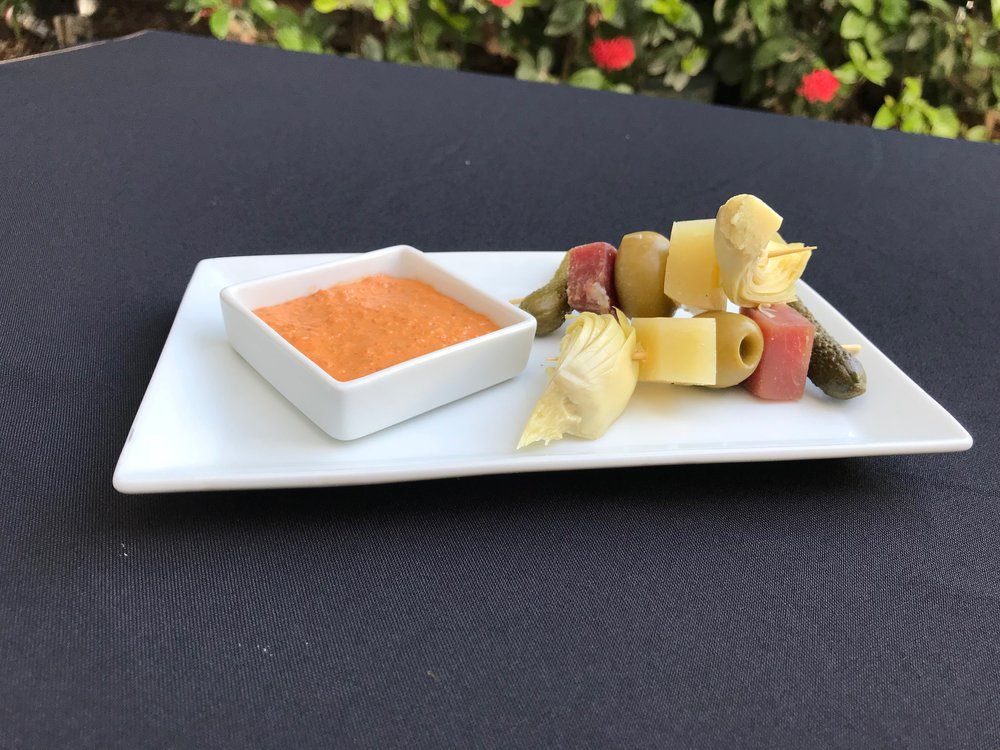 Antipasto  - Skewered marinated artichoke, gherkins, manchego, Serrano ham, and olives, served with an oven-roasted tomato sauce