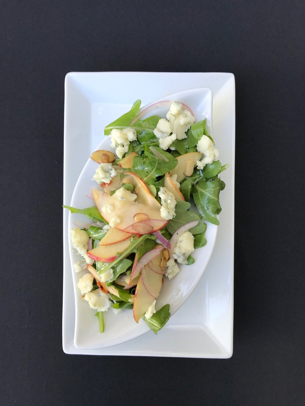 Roquefort & Arugula Salad - Fresh baby arugula tossed with apples, celery, sliced almonds, and a housemade vinaigrette and topped with Roquefort cheese
