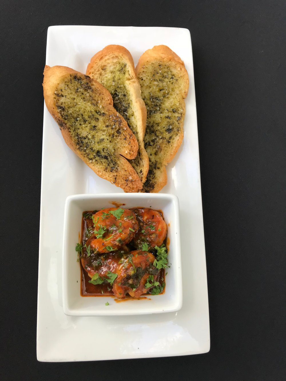 Moroccan Shrimp - Sautéed shrimp in a harissa paste, with ginger, cumin, coriander, and parsley. Served with a basil infused olive oil crostini