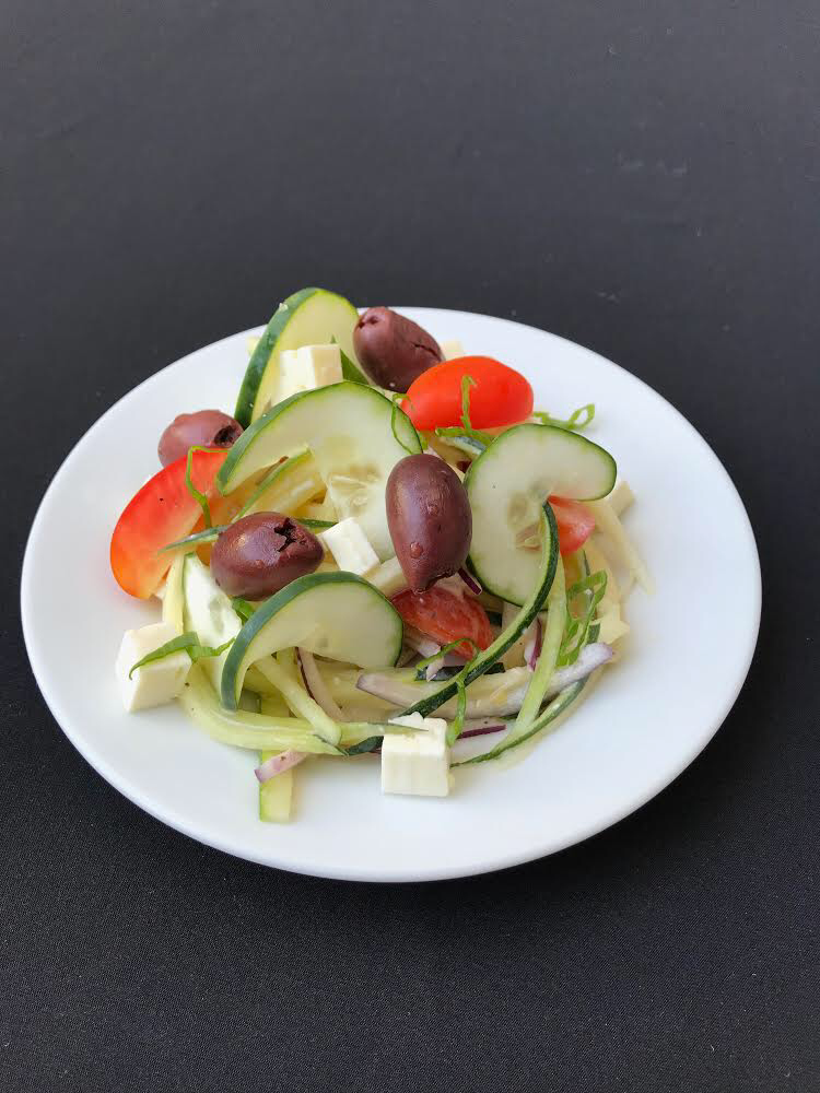- Zucchini Noodle Strings of zucchini with Kalamata olives, feta cheese, tomato, and cucumber with a spicy-tangy Greek yoghurt dressing