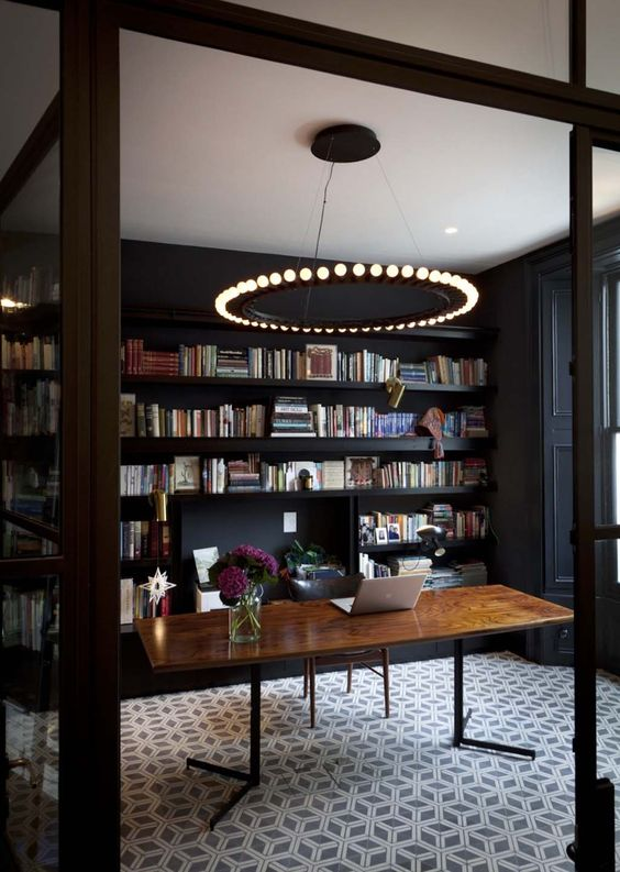 home office with black walls, built in shelving