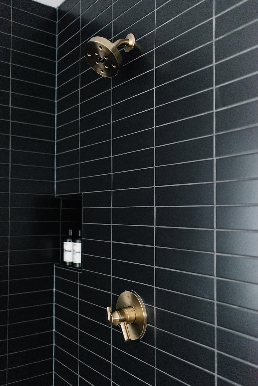 black subway tile in shower, delta trinsic brass shower fixture