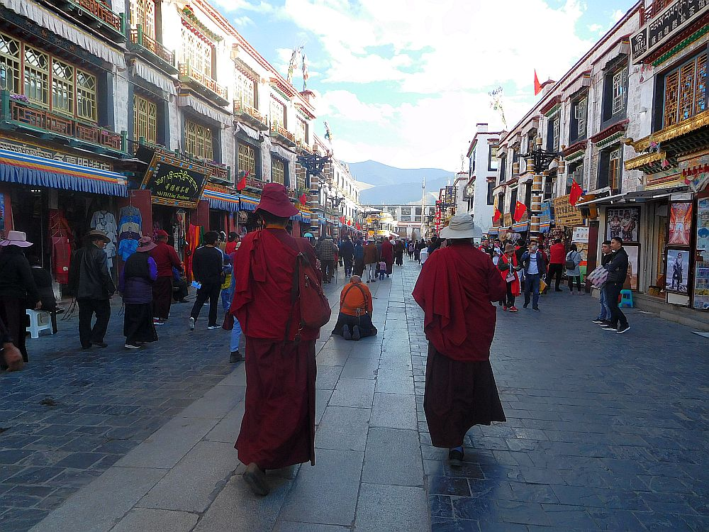 Evening: people walking the kora in Lhasa, including two monks and a man kneeling in prostration.