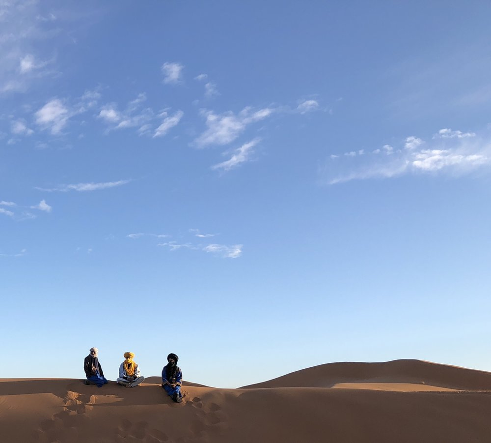 Three Berbers watch the day's camel preparations just after sunrise.