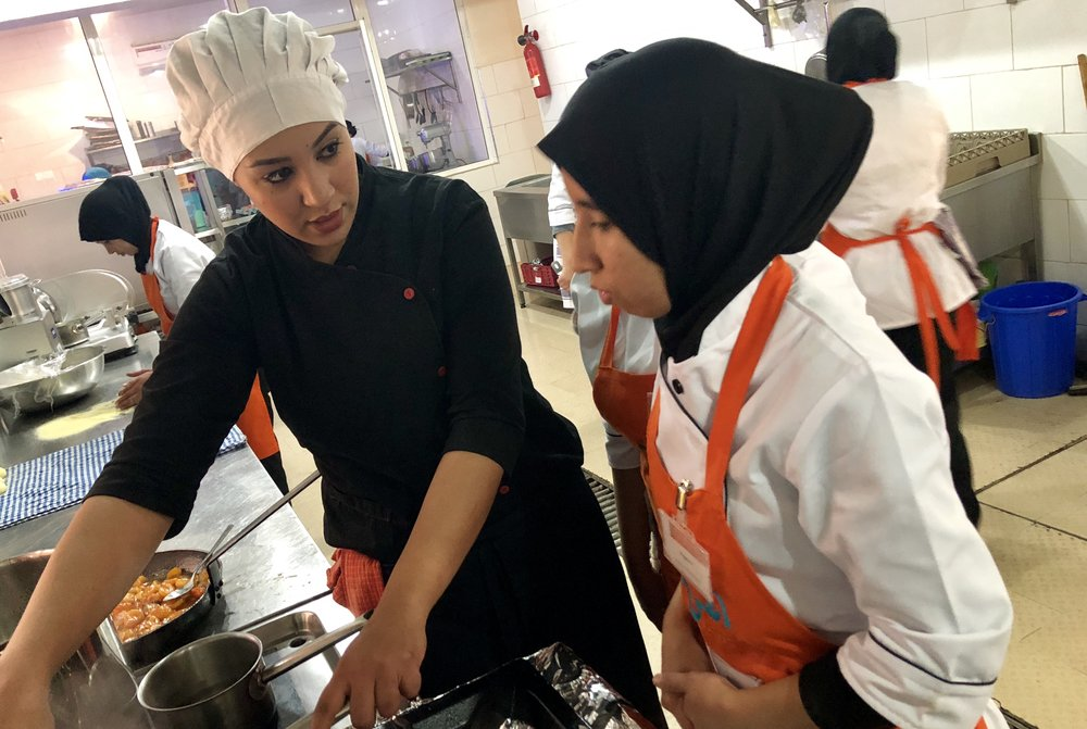 Chef du Cuisine Karima instructs a trainee as the kitchen at Amal Targa prepares hundreds of hors d'oeuvres for a catered party.