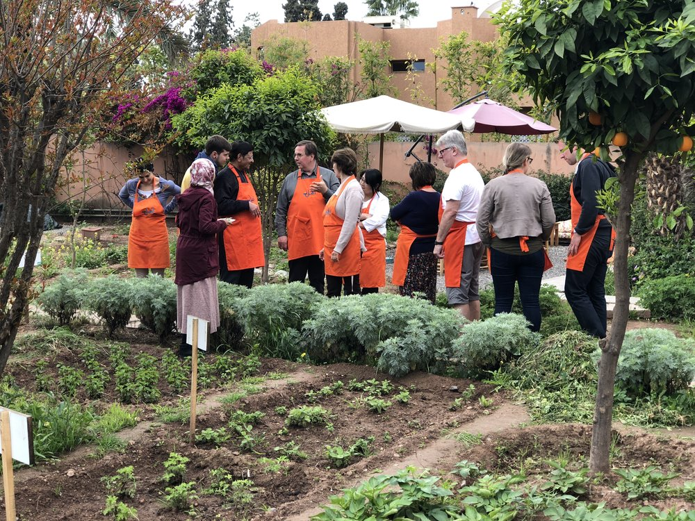 In the garden at Amal Targa, Warda explains their environmental and conservation practices to tourists enrolled in a tajine cooking class.