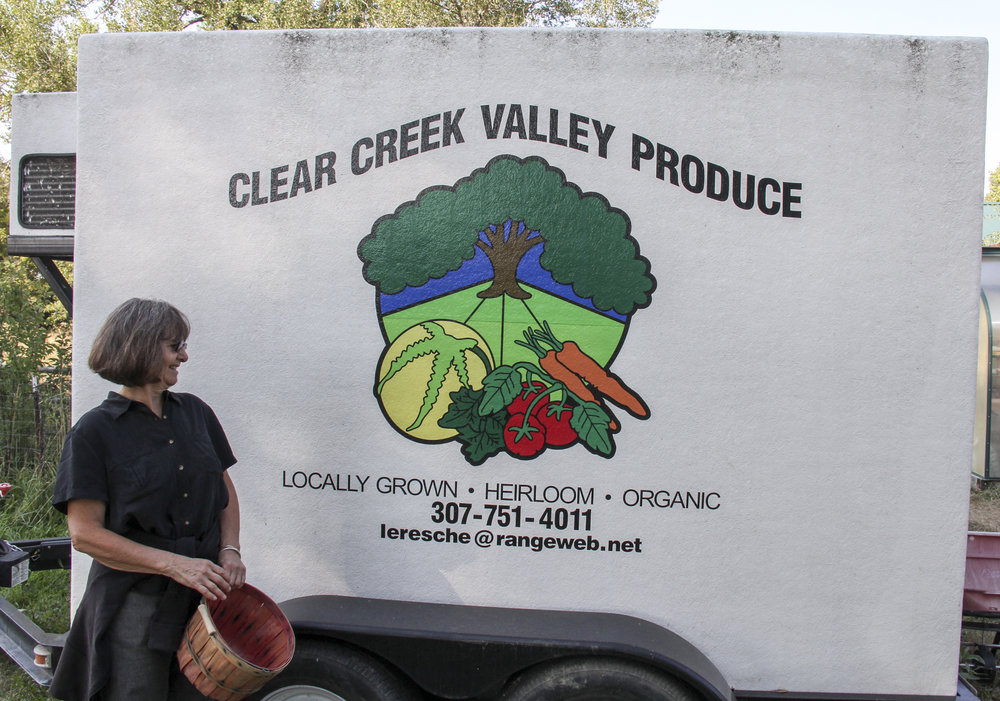 """Carol stands in front of her refrigerated trailer near her garden. """"I'm growing vegetables...I am all involved in food and what it means and how it's important in a community,"""" says Carol."""
