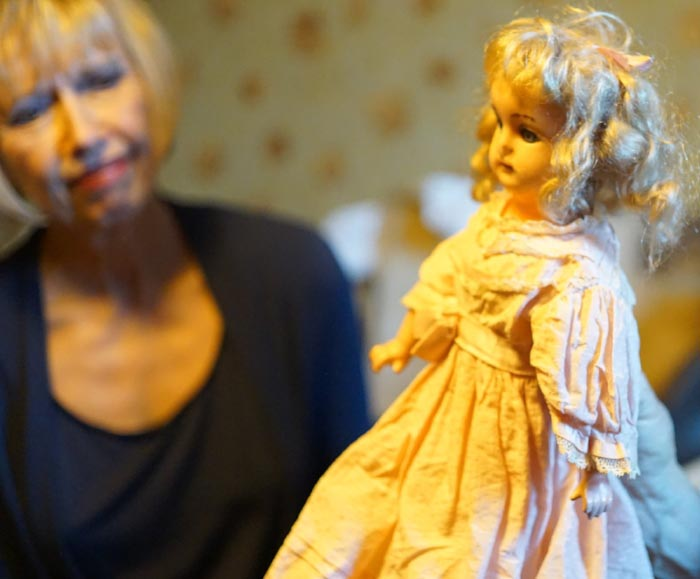 Paulette gazes at one of the antique dolls in the house with a look of interest and trepidation. ( JS )