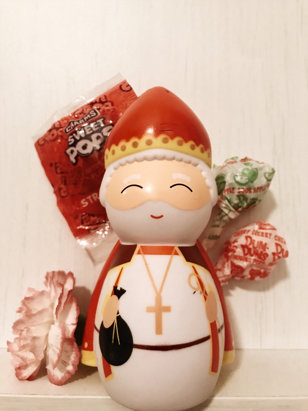 Saint Nicholas Shining Light doll's about to be dropped into a cute little toddler shoe with some lollipops.