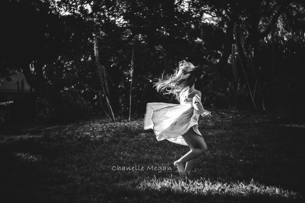 A young child embracing the wind through her hair and dress as she runs across the lawn in it.