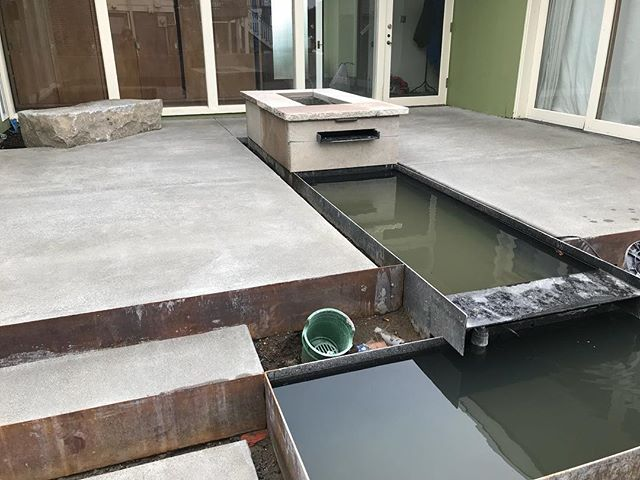 Work in progress. Metal trough water feature. Water spills out of fire pit up top. #midcenturycourtyard