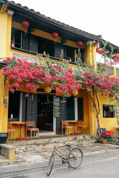 Yellow building covered in pink and red bougainvillea with charming cafe chairs and a bike parked out front in Hoi An Vietnam. The French mixed with the Vietnamese.