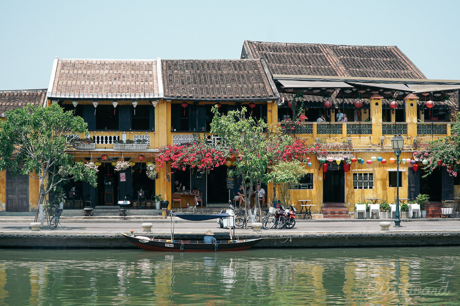 French influenced yellow buildings line the river in Hoi An Vietnam. Bikes and trees scatter the walk way as boats cruise up and down the river waiting for tourists to buy a ride