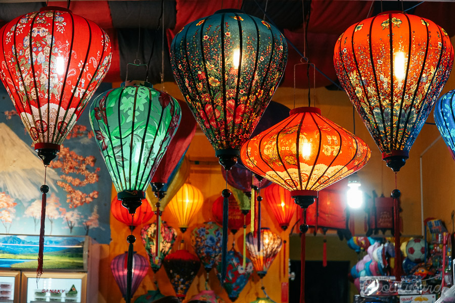 Intricately patterned lanterns light up the street at night in Hoi An Vietnam