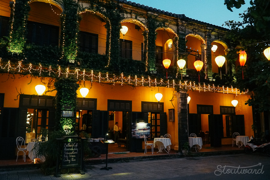 An evening shot of a yellow cafe covered in ivy vines with cafe seating show the French influence in Hoi An Vietnam.
