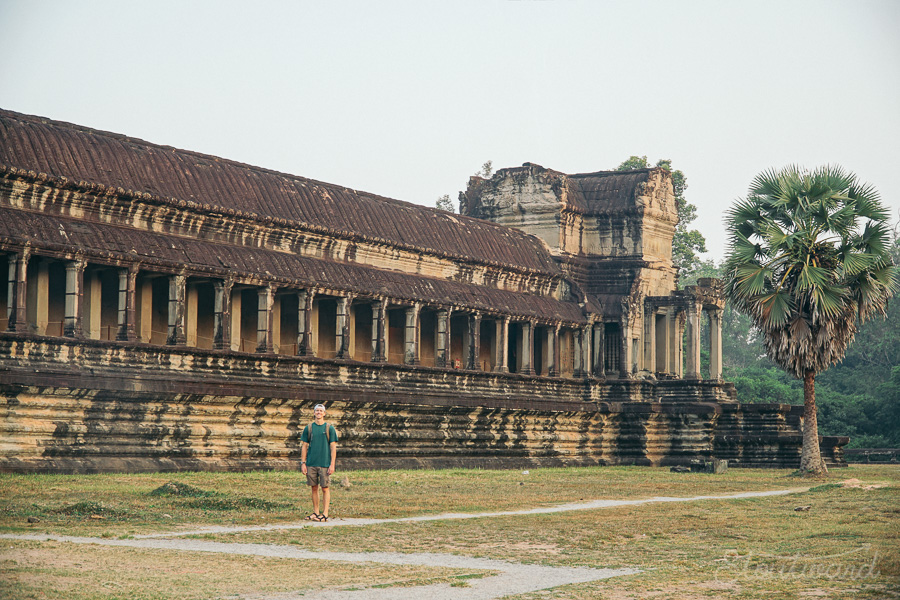 man with backpack in front of outer western gate of angkor wat in siem reap cambodia among grass and a palm tree.