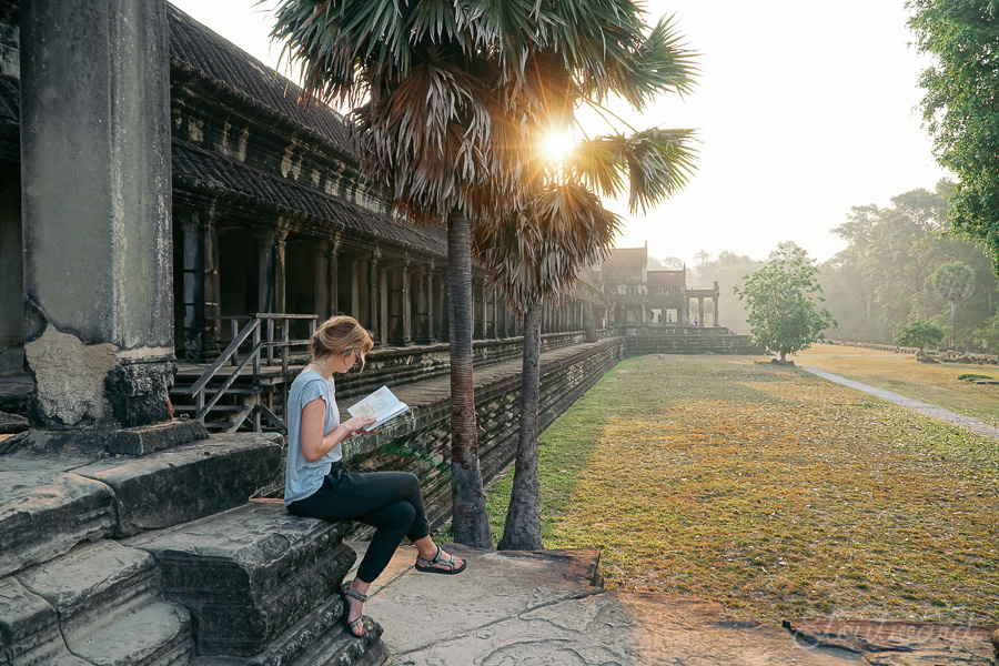 Kelsey (girl) reading a guidebook on the steps of the north gate of ankor wat in early morning sun light among grass and palms in siem reap cambodia.