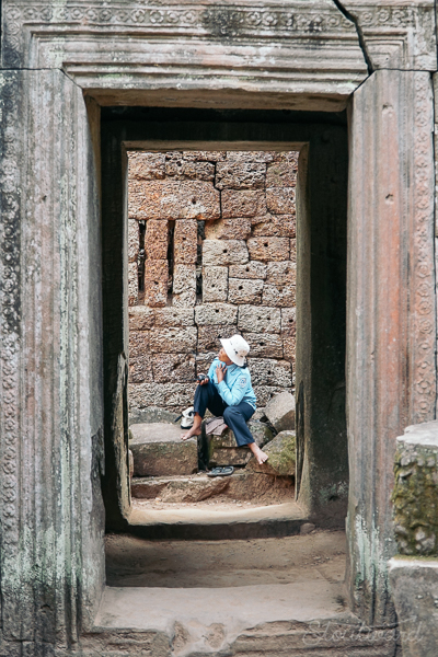 local cambodian guide rests at Ta Prohm temple (tomb raider temple) in angkor area of siem reap cambodia.
