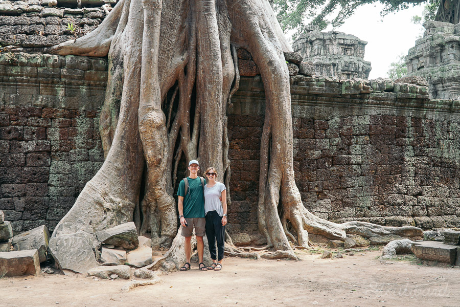 Kelsey and Andrew in front of trees growing into ruins at Ta Prohm temple (tomb raider temple) in angkor area of siem reap cambodia.