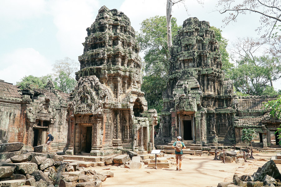 two towers with tourist man and backpack in the Ta Prohm temple in the Angkor area of Siem Reap, Cambodia.
