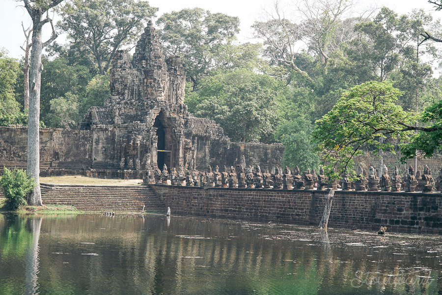 south gate over the water of the moat to angkor thom in siem reap cambodia.