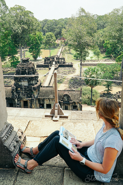 Kelsey (woman) reading on top of Baphuon in angkor thom area of siem reap cambodia.