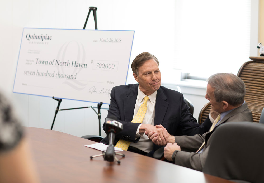 Quinnipiac President John Lahey presenting check to North Haven First Selectmen Michael Freda.  Photo Via Quinnipiac University Photographer Autumn Driscoll